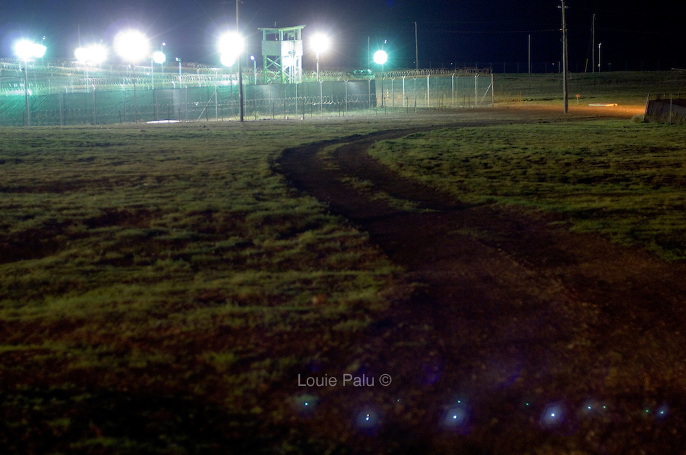 """A night view of a dirt road which snakes its way toward the Camp Delta detention facility in Guantanamo Bay. The U.S. Government is currently holding approximately 340 """"enemy combatants"""" in Guantanamo Bay, Cuba. They were captured during the """"Global War on Terrorism"""" after the attacks on the United States on September 11, 2001. This photo was reviewed by a U.S. Military official before transmission."""