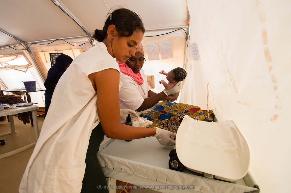 Care Assistant, Fatimata Walet Ali, and Midwife, Viola Nizigiyimana,  weighing a healthy baby boy moments after he was born at a Médecins Sans Frontières (MSF) health centre at the Mbera camp for Malian refugees in Mauritania, on 5 March 2013. (In keeping with tradition, the baby will not be named until he is a week old.)