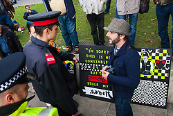 "Parliament Square, London, October 25th 2014. Activists from Occupy Democracy continue their small protest against ""capitalism's usurping of democracy"", outside Parliament. They demand that the government puts ""people before profit"" and that the proposed TTIP protocol between Europe and the US is dropped, and that attempts to further privatise the NHS and other public services are stopped. Heritage Wardens from the GLC continue with the support of dozens of police officers to keep the protesters on the periphery of parliament square, occasionally taking banners and posters from the protesters. PICTURED: A Heritage Warden, charged with security for Parliament Square demands that an artist removes his paintings from Parliament Square."