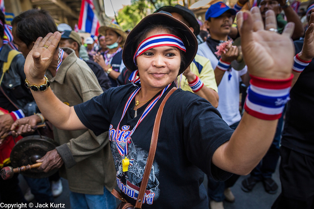"14 JANUARY 2014 - BANGKOK, THAILAND: Anti-government protestors play drums and dance on Rama I Road in front of Royal Thai Police headquarters. Hundreds of protestors picketed police headquarters because they accuse the police of siding with the government during the protests. Tens of thousands of Thai anti-government protestors continued to block the streets of Bangkok Tuesday to shut down the Thai capitol. The protest, ""Shutdown Bangkok,"" is expected to last at least a week. Shutdown Bangkok is organized by People's Democratic Reform Committee (PRDC). It's a continuation of protests that started in early November. There have been shootings almost every night at different protests sites around Bangkok, but so far Shutdown Bangkok has been peaceful. The malls in Bangkok are still open but many other businesses are closed and mass transit is swamped with both protestors and people who had to use mass transit because the roads were blocked.     PHOTO BY JACK KURTZ"