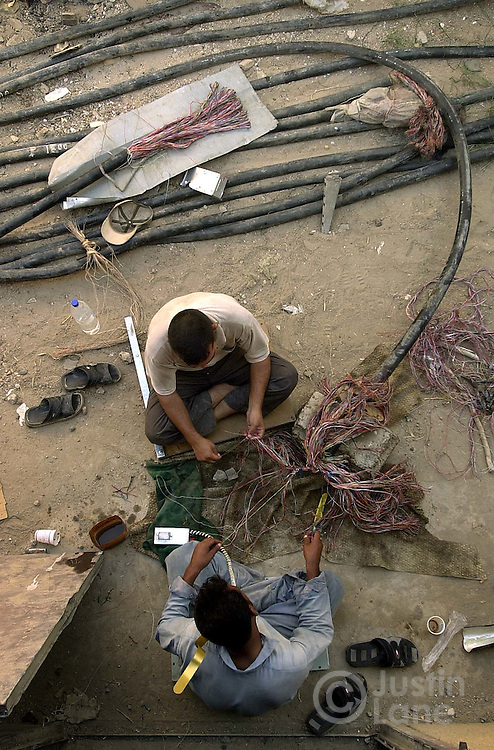 10/01/03--Baghdad, Iraq--FOR RECONSTRUCTION STORYTwo men work on reconstructing Baghdad's telephone system. Each line, and there are thousands, need to be spliced and tested. this is part of the massive effort to get Baghdad's infrastructure repaired.