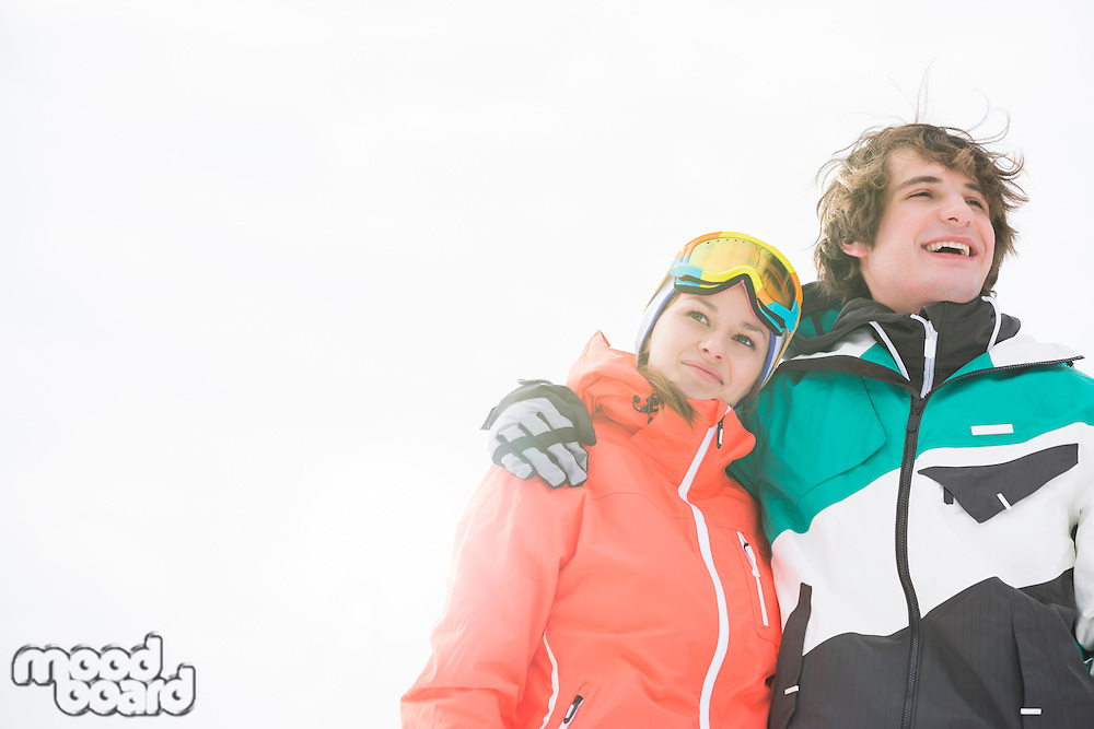 Loving young couple in warm clothing against clear sky