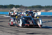 The No.2 Audi driven by Alan McNish, Dindo Capelli, and Tom Kristensen leads its sister car and others through a chicane at Sebring.