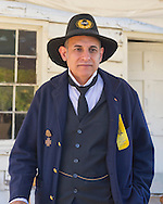Old Bethpage, New York, U.S. 29th September 2013. A Civil War re-enactor is wearing a reproduction of a yellow Reunion Ribbon for the Grand Army of the Republic, Moses Baldwin Post 544, at The Long Island Fair. A yearly event since 1842, the county fair is now held at a reconstructed fairground at Old Bethpage Village Restoration.