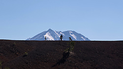Father and two children hike along the rim of Cinder Cone with Lassen Peak in the background, Lassen Volcanic National Park, California, United States of America