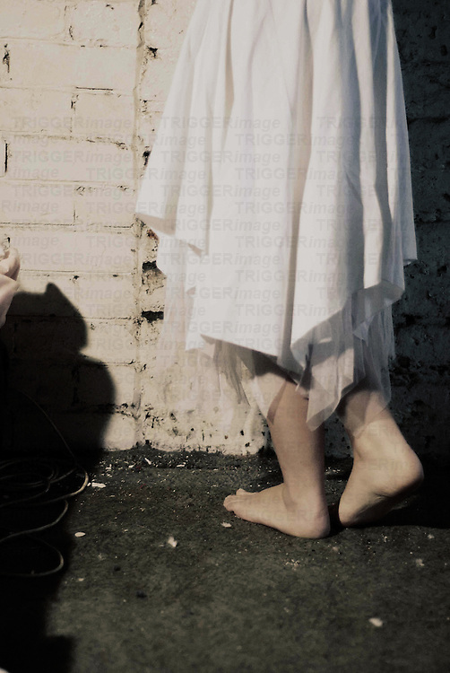 A young womans legs covered with a white skirt