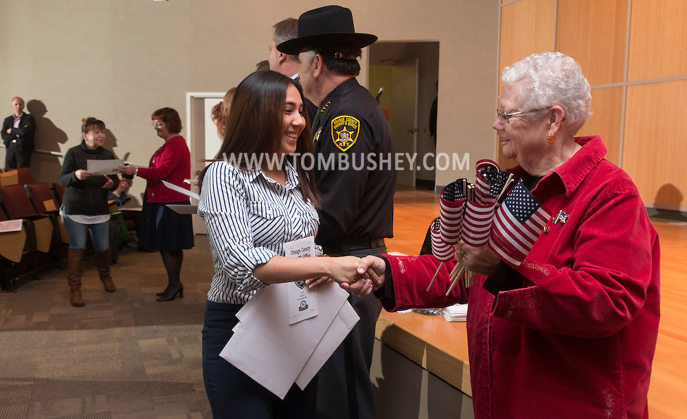 Goshen, New York - A member of the Daughters of the American Revolution shakes hands with a new American citizen during a Naturalization ceremony at the Orange County Emergency Services Center on Nov. 17, 2016.