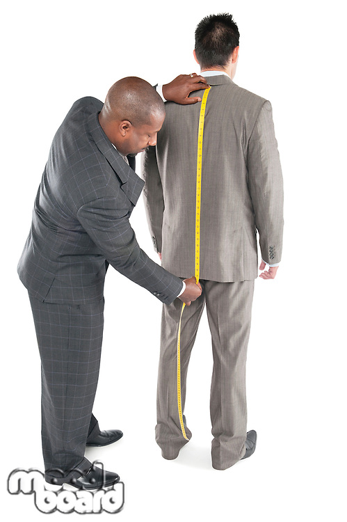 Male tailor fitting a man with a suit over white background