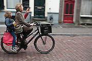 Een moeder fietst met haar kind achterop door Utrecht.<br /> <br /> A mother is cycling with her child in Utrecht.