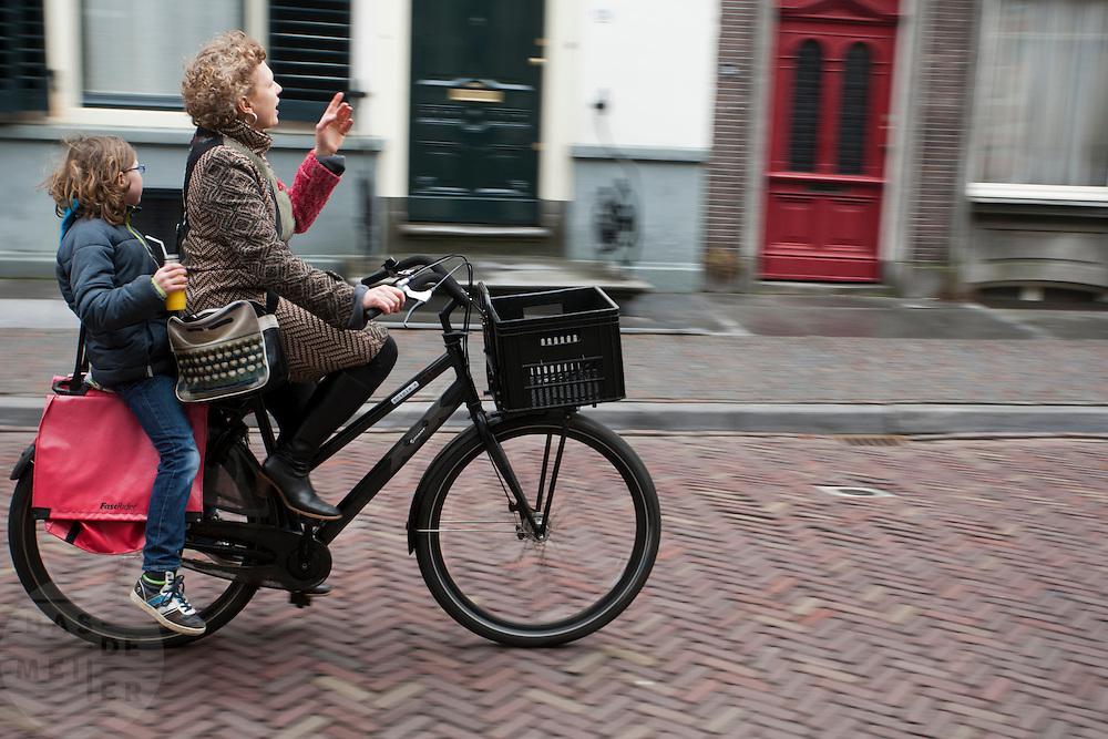Een moeder fietst met haar kind achterop door Utrecht.<br /> <br /> A mother is cycling with her child in Utrecht.
