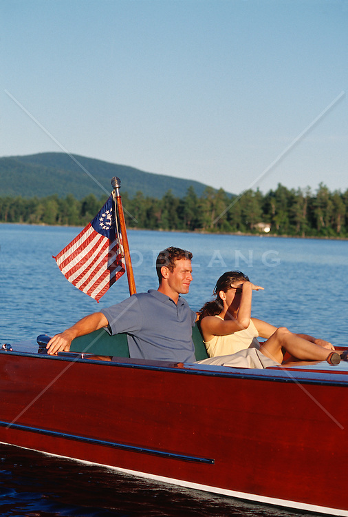 Young wealthy couple In A Wooden Motor Boat enjoying a ride on a lake in New Hampshire