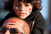 31 JANUARY 2011 - TEMPE, AZ: OSAMA ABDALLAH carries his son ADAM during a demonstration in Tempe, AZ, Monday in support of democracy in Egypt. About 200 people marched through central Tempe, AZ, near the Arizona State University campus Monday afternoon. The rally was organized by the Arab American Association of Arizona in solidarity with the ongoing pro-democracy rallies and demonstrations in Egypt and other Arab countries.    Photo by Jack Kurtz