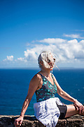 A middle aged woman enjoying the sun and view from high atop a hill in Guadeloupe looking over the sea to Caribbean islands