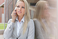 Beautiful blond businesswoman conversing on cell phone while looking away by glass wall