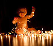 Child in diapers enthralled with (safe, low-voltage) Christmas tree lights, sitting on a reflective floor which causes the lights to streak. Child is smiling at camera/viewer.