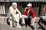 FRANCE, PARIS, MONTMARTRE A mime artist and a house painter share a smoke outside the Basilique du Sacre-Coeur