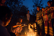 Displaced Rengma-Naga villagers gather for a cup of tea at dusk in the Borpathar High School relief camp in the Karbi Anlong district of Assam. With no motor able roads leading to the jungle villages, Rengma-Naga and Karbi villagers had to walk up to 8 miles carrying out their children and possessions. Image © Jonah Markowitz/Falcon Photo Agency