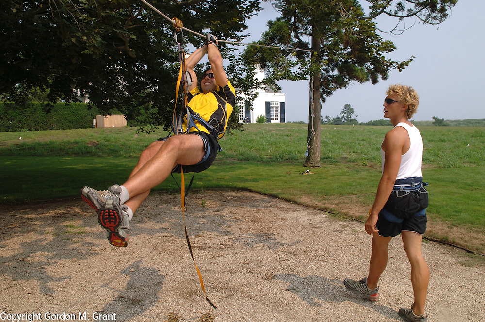 Water Mill, NY - 8/13/05 - Juris Kupris, right, a personal trainer, works with his client, Mike DePaola, left, on a zip line at his clients home in Water Mill, NY August 13, 2005.     (Photo by Gordon M. Grant)<br />