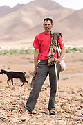 A Berber nomadic shepherd herds goats amid arid terrain near Aoulouz, Taliouine & Taroudant Province, Souss Massa Draa region of Southern Morocco, 2016-05-21. <br />