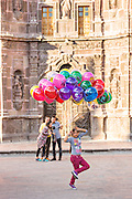 A young girl sells balloons in the Plaza de la Soledad by the Nuestra Señora de la Salud Church in the historic center of San Miguel de Allende, Mexico.