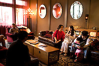 """NAMES CQ: Amy Liu, center, and Michelle Xiao, right, chat on the couch, as Kirk Wang, and daughter Kasey, 3, far right, read a book in the lounge of Avia Napa, along First Street, in downtown Napa, Ca., on Saturday, May 22, 2010. Recent development along First Street includes a new boutique hotel, restaurants, and tasting rooms has helped revitalize Napa's downtown, which has recently been coined the """"West End."""""""