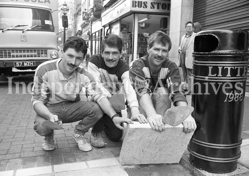 The last granite slab being laid in Grafton St. It was put into place by Nicky Whelan, left, and brothers Vincent, centre, and Damien McConnell of Ridgedale Construction who paved the street. 28/06/1988. 688-709 (Part of the Independent Newspapers Ireland/NLI Collection)