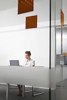 Woman using laptop behind glass door