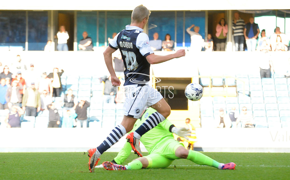 Steve Morrison chips in Millwall's third during the Sky Bet League 1 match between Millwall and Rochdale at The Den, London, England on 26 September 2015. Photo by Michael Hulf.