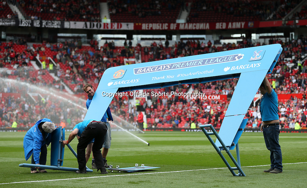 14th September 2013 - Barclays Premier League - Manchester United v Crystal Palace - Workers construct the Barclays on-pitch hoarding prior to kick-off - Photo: Simon Stacpoole / Offside.