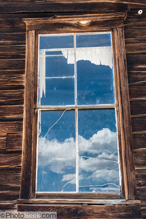 "An old window reflects cumulus clouds at Bodie, California's official state gold rush ghost town. Bodie State Historic Park lies in the Bodie Hills east of the Sierra Nevada mountain range in Mono County, near Bridgeport, California, USA. After W. S. Bodey's original gold discovery in 1859, profitable gold ore discoveries in 1876 and 1878 transformed ""Bodie"" from an isolated mining camp to a Wild West boomtown. By 1879, Bodie had a population of 5000-7000 people with 2000 buildings. At its peak, 65 saloons lined Main Street, which was a mile long. Bodie declined rapidly 1912-1917 and the last mine closed in 1942. Bodie became a National Historic Landmark in 1961 and Bodie State Historic Park in 1962."