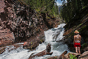 A young woman enjoys the solitude at Mineral Creek just outside of Silverton, Colorado.