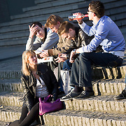 Nederland Rotterdam 21-03-2009 20090321Foto: David Rozing ..Groep mannen en 1 vrouw genieten van het mooie weer en drinken rose uit de fles op de trappen van het wtc, centrum rotterdam. Daily life, youth drinking wine in public space , on street in city of Rotterdam Foto: David Rozing
