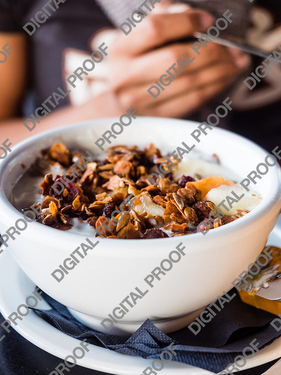Eating healthy breakfast bowl. Yogurt, granola, seeds, fresh and dry fruits woman' s hands at background. Clean eating, dieting, detox, vegetarian food concept