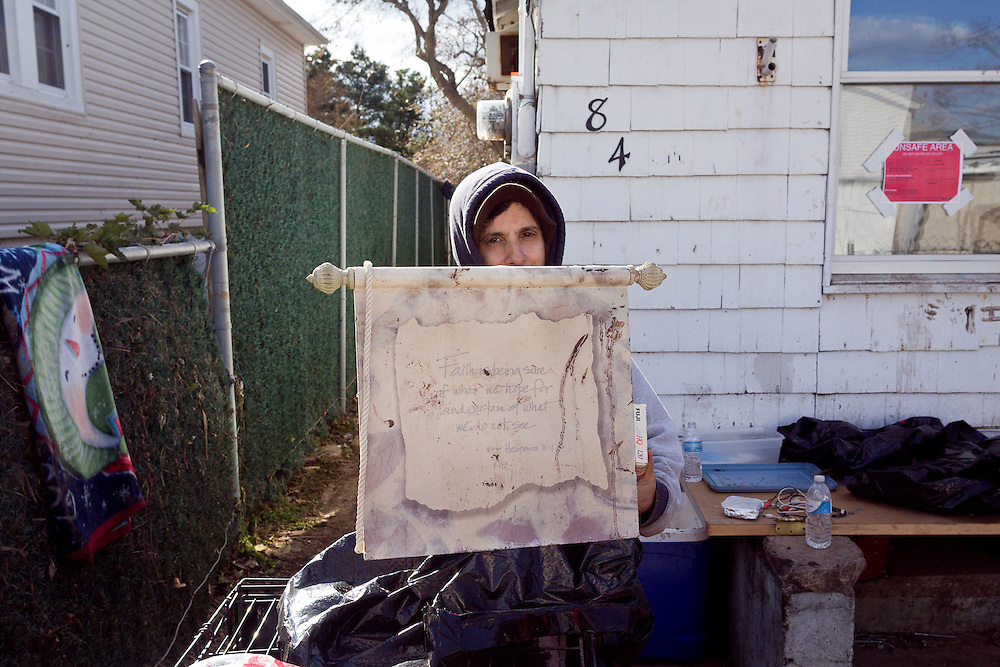 Nilda Palumbo retrieved precious belongings, including photo albums and her son's high school yearbooks, from her condemned home on Tarlton Ave. The water mostly filled the bungalow.