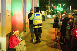 "© Licensed to London News Pictures . 24/12/2016 . Manchester , UK . Police push a man back from a fight , on Withy Grove . Revellers out in Manchester City Centre overnight during 2016's second "" Mad Friday "" , named for historically being one of the busiest nights of the year for the emergency services in the UK . Photo credit : Joel Goodman/LNP"