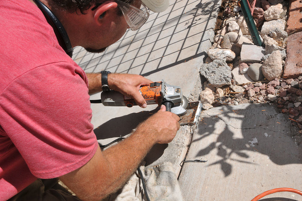 Tucson's Green Handyman, Jesse Micander, grinds a metal piece that used to support a porch post.