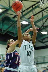 06 December 2017:  Devin Kyler can't stop the shot by Raven Hughes during an NCAA women's basketball game between the Wheaton Thunder and the Illinois Wesleyan Titans in Shirk Center, Bloomington IL