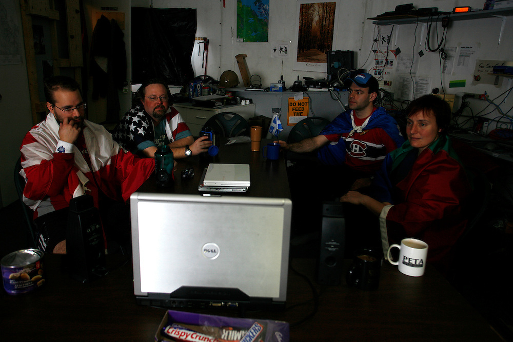 From left to right  Ryan Kobrick -27 James Harris ? 38 Simon Auclair -24 Kim Binsted ? 37 watching the final hockey game between Canada and the USA, throw the internet wean the rest on the teem eating dinner. in the FMARS (Flashline Mars Arctic Research Station),..On Devon Island Canada.  Monday  June, 4, 2007.....Mars flashline Mars arctic (FMARS)....On Devon Island in the high Canadian Arctic a group of sciences from the USA & Canada is gathering for four month to search watt human being can do on mars planet...The four month mission will be the first time that a simulated Mars mission has ever been conducted for such a long duration...The crow of volunteers includes some biologist geologist and other nether scientist researches.....They chose Devon Island in Canada because it simulated the acclaim on the planet Mars, for getting the filling of being on Mars and to challenge the research and to make it close as they can to the conditions on the planet they wear spies suit and live isolated in the laboratory for four month...The man person that ran the project is Dr Robert Zabrin that believe that this project can lied to find ways to search for life on Mars and maybe to fined a way that human being will be able to live on the planet.....This project is privet projects that cooperate with several universities around the world.....