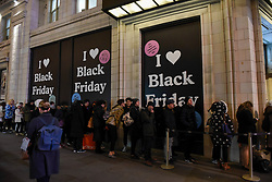 © Licensed to London News Pictures. 23/11/2018. LONDON, UK.  People queue into the night outside the UGG store in Piccadilly Circus on Black Friday. Traditional retailers face increasing challenges to attract customers against their online competition.  Photo credit: Stephen Chung/LNP