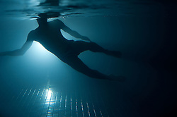 Swimmer in a pool taken from underwater against the light
