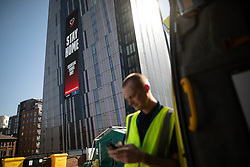 © Licensed to London News Pictures . 21/04/2020. Manchester, UK. Cleaners employed to deep clean ambulances after carrying coronavirus patients are pictured outside the hospital with an advert advising people to STAY HOME on a big screen on the face of Manchester's Axis Tower building . The National Health Service has built a 648 bed field hospital for the treatment of Covid-19 patients , at the historical railway station terminus which now forms the main hall of the Manchester Central Convention Centre . The facility is treating patients from across the North West of England , providing them with general medical care and oxygen therapy after discharge from Intensive Care Units . Photo credit : Joel Goodman/LNP