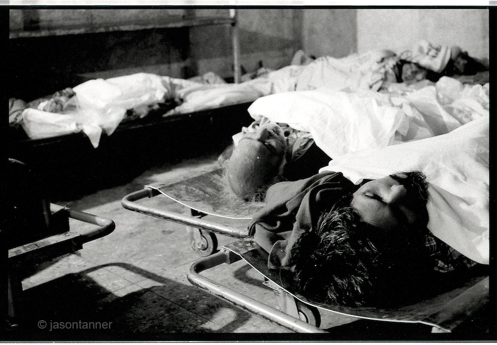 Karachi: An unclaimed, and unidentified bodies of men at an Edhi morgue facility in Karachi...The Edhi foundation morgue facility in Karachi sometimes receives around 30-50 deceased persons on a daily basis. the are kept in cold storage facilities for 3-4 days until they are either claimed by relatives of released for burial. Most are homeless or poor people whilst others victims of the many fatal road traffic accidents that occur in the city on a daily basis...In a country of some 160 million people, affordable medicines and diagnostic tests are beyond the reach of most people in Pakistan. The country suffers from shortage of doctors and government funded healthcare facilities; to many  on low income levels, basic health care is a luxury. The rich and middle class get the best treatment whilst the poor reply on the work of a welfare trust by the name Edhi Foundation. ..The Edhi foundation was established by Abdul Sattar Edhi. Born in a small Indian own of Bantva in the province of Gujrat he migrated to Pakistan during partition in 1947. After working as a commissioning agent selling cloth in a market in Karachi Abdul Sattar Edhi and other members of his community decided to establish a free dispensary in the city. Disillusionment with the lack of health care led him to establish a welfare trust of his own called the Abdul Sattar Edhi Foundation. Appeals were made, funds raised and soon a home was established and a number of ambulances patrolled the streets of Karachi...In 1965 Adbul married a nurse working at the foundation, Bilquis. They have four children and all are involved in the current day to day running of the foundation. Bilquis Edhi runs a maternity home at the headquarters in Karachi and organises the adoption of illegitimate children and abandoned babies. The family share the foundation's vision of a single minded devotion to the cause of alleviation of human sufferings and a sense of personal responsibility. The foundation responds for calls of help