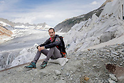 Glaciolog David Volken at the mouth of the Rhone Glacier.<br /> Huge sheets with fleece blankets that cover an ice tunnel at the mouth of the Rhone Glacier in Switzerland. After a winter with record amounts of snow, most of it was gone when this imae was taken on July 14th 2018, exposing the darker ice. While snow is a brilliant reflector of the energy from the sun, the darker ice absorbs the energy instead, accelerating the melting of the glacier. The color and darkness of glacier ice vary all over the world, depending on build-up of pollution, age of the ice, particles picked up by the ice and by microorganisms in the ice. The glacier ice is however rarely white as snow. With shorter winters and vanishing snow cover, the melting of the glaciers is accelerating.<br /> The Rhone Glacier now melts more than 70 centimeters in thickness every week during the summer months. Between 1996 and 2006, an estimated 0.9 billion cubic metres of water melted yearly from the Swiss glaciers. That number is likely much higher today. Switzerland just had the hottest July since 1921, and the rivers are running at record low levels.<br /> The ice tunnel is a popular tourist attraction, and has been a steady income source for the Carlen family who runs and maintain the ice tunnel. The fleece blankets help slow down the melting. While tourists always have flocked to the Rhone Glacier due to it's easy access from the nearby Furka Pass, today's tourism is often visitors who are concerned about the effects of climate change.