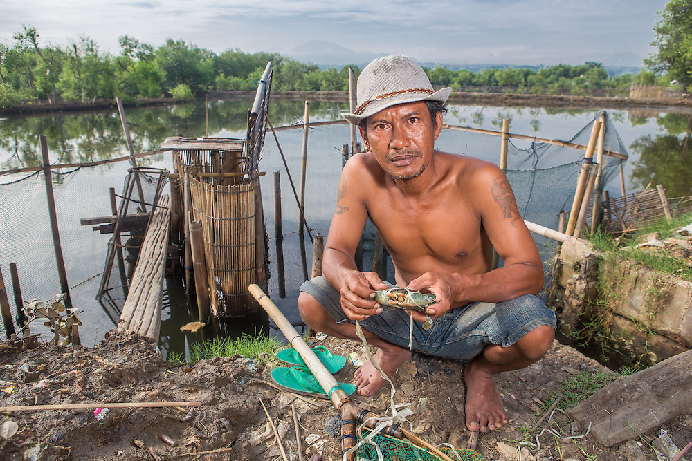 CAPTION: Sugeng is a fish and crab farmer from Tapak village. Like many of the local fish farmers, his family relies heavily upon the income generated through fish farming. Each time it floods, he experiences huge financial losses and has to search for wage labour. LOCATION: Tapak, Semarang, Indonesia. INDIVIDUAL(S) PHOTOGRAPHED: Sugeng.