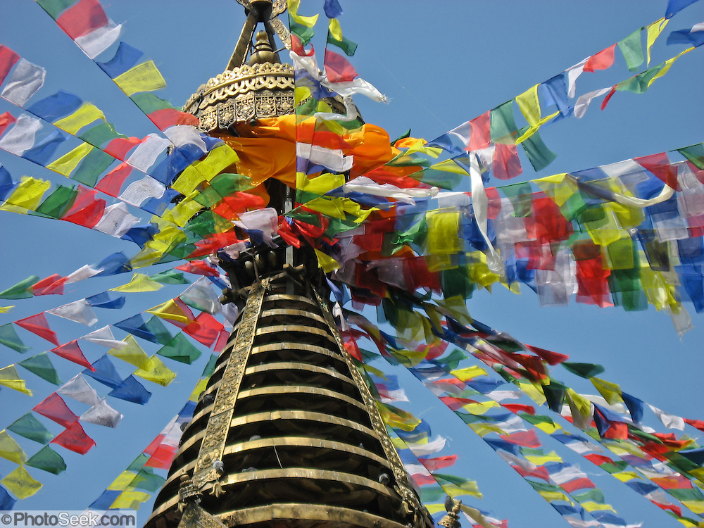 "Carol Dempsey photographed this closeup of the Tibetan Buddhist prayer flags attached to the top of Kathesimbhu. Kathesimbhu means ""Kathmandu Swayambhu"". This 17th century stupa (bell-shaped Buddhist monument) in Kathmandu, Nepal, is a smaller version of the more famous ""Monkey Temple"" at Swayambhu. A walk around the Kathesimbhu stupa promises the old and lame the same blessings as a pilgrimage to Swayambhunath's hill. This spire has 13 gilded disks representing the 13 steps to Buddhist enlightenment, and enlightenment is represented by the top-most umbrella."