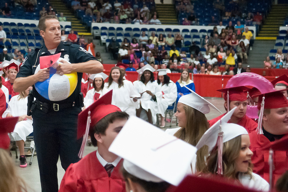 Lathan Goumas | MLive.com..A Swartz Creek police officer tears open a beach ball to deflate it during the 2012 Swartz Creek High School commencement ceremony at the Perani Arena in Flint, Mich. on Tuesday June 12, 2012.