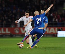 Gareth Bale of Wales (Real Madrid) is tackled by Hallfredsson of Iceland  - Photo mandatory by-line: Dougie Allward/JMP - Tel: Mobile: 07966 386802 03/03/2014 -