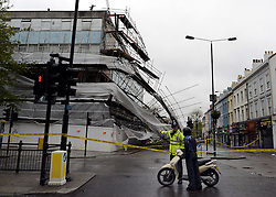 © Licensed to London News Pictures. 29/04/2012. London, UK . A police man directs a motorbike rider. Heavy winds have caused a large section of scaffolding to collapse on building work being carried out for a new Jamie Oliver restaurant on Notting Hill Gate in West London today 29th April 2012. The structure came down at approx 0300am across a main road junction and nobody was hurt. The  Photo credit : Stephen Simpson/LNP