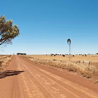 Hot dusty road across flat landscape with water vane