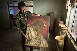 © Licensed to London News Pictures. 04/11/2016. Hamdaniyah, Iraq. A Christian militiaman, holds up a picture of Jesus Christ, slashed by Islamic State militants who previously occupied the house, in the recently liberated town of Hamdaniyah, Iraq. The house was also used as a factory for constructing improvised mines, components can be seen stacked on the right side of the image.<br /> <br /> Although located close to a front line, littered with improvised explosive devices and pieces of unexploded ordnance the Christian town of Hamdaniyah has only recently been cleared of ISIS extremists who stayed behind to fight. After the town's liberation as part of the Mosul Offensive residents and priests of the town are now free to take short trips to assess damage, salvage possessions and clear up the mess left by militants during their two year occupation.<br /> <br /> Hamdaniyah, and much of the Nineveh plains, were captured by the Islamic State during a large offensive on the 7th of August 2014 that saw the extremists advance to within 20km of the Iraqi Kurdish capital Erbil. Residents of the town, who included many Christian refugees who escaped there after the fall of Mosul, were then forced to seek sanctuary in the Kurdish areas. In the year and two months of the ISIS occupation churches were burnt, homes were put into use as militant accommodation and bomb factories and some buildings destroyed by coalition airstrikes. Photo credit: Matt Cetti-Roberts/LNP